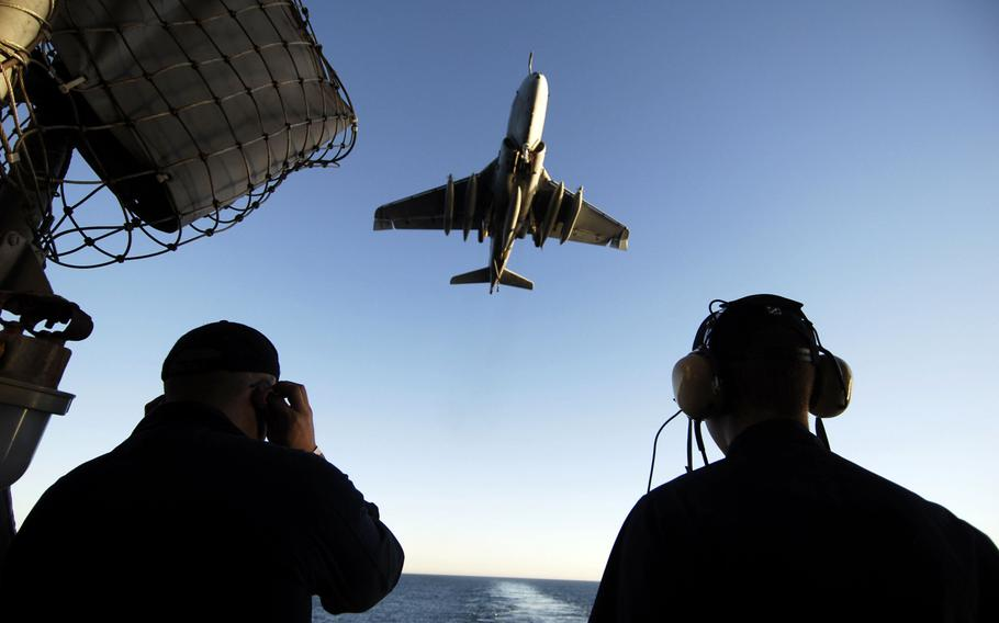 Seaman Chris Cardenas, left, and Boatswain's Mate Seaman Guillermo Mercado, right, stand aft lookout watch on the fantail of the aircraft carrier USS John C. Stennis as an EA-6B Prowler from the ''Yellow Jackets''' of Electronic Warfare Squadron 138 comes in for an arrested landing January 17, 2009.