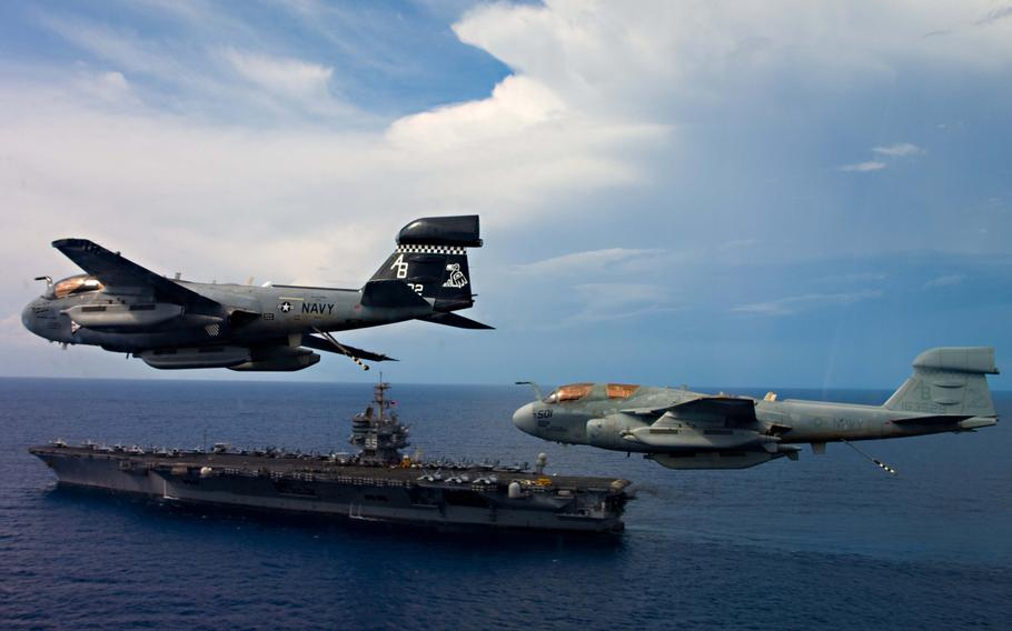 Two EA-6B Prowlers assigned to the ''Rooks'' of Electronic Attack Squadron 137 fly in formation over the aircraft carrier USS Enterprise on October 15, 2012.
