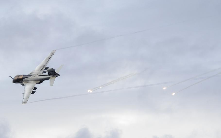 An EA-6B Prowler, assigned to the ''Gray Wolves'' of Electronic Attack Squadron 142, shoots flares as it passes the aircraft carrier USS Nimitz during an airshow performed by the squadrons of Carrier Air Wing 11 on December 7, 2013.
