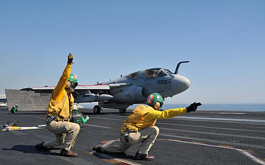 Lt. Robert Arndt, left, and Lt. Christopher Cannon, right, give the signal to launch an EA-6B Prowler assigned to the ''Garudas'' of Electronic Attack Squadron 134 off the flight deck of the aircraft carrier USS George H.W. Bush on June 19, 2014.