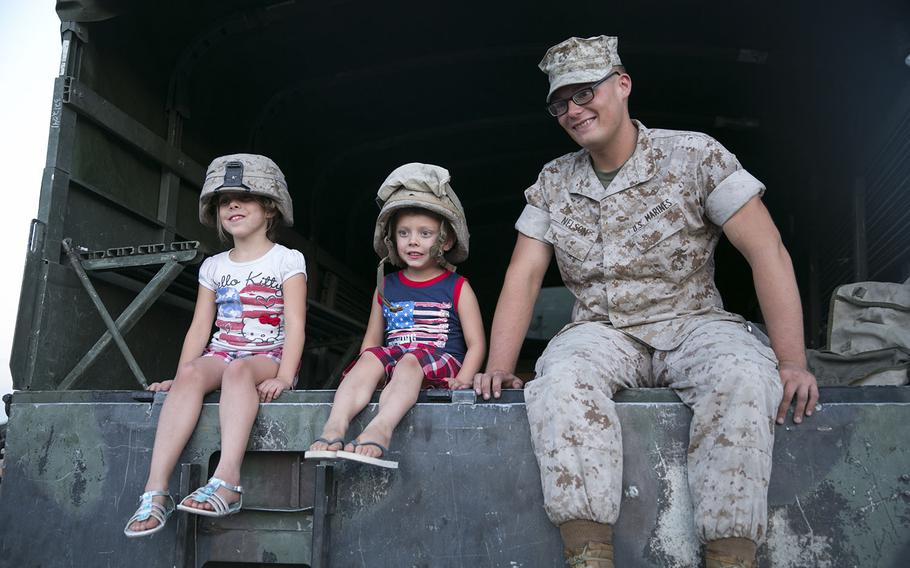Pvt. Christopher Nelson, field artillery cannoneer, sits in a Medium Tactical Vehicle Replacement with Gracie Lynn Sandefur, 7, and Bentley Sandefur, 5, at the Community Center Park during the Yucca Valley Independence Day Celebration, July 4, 2015.