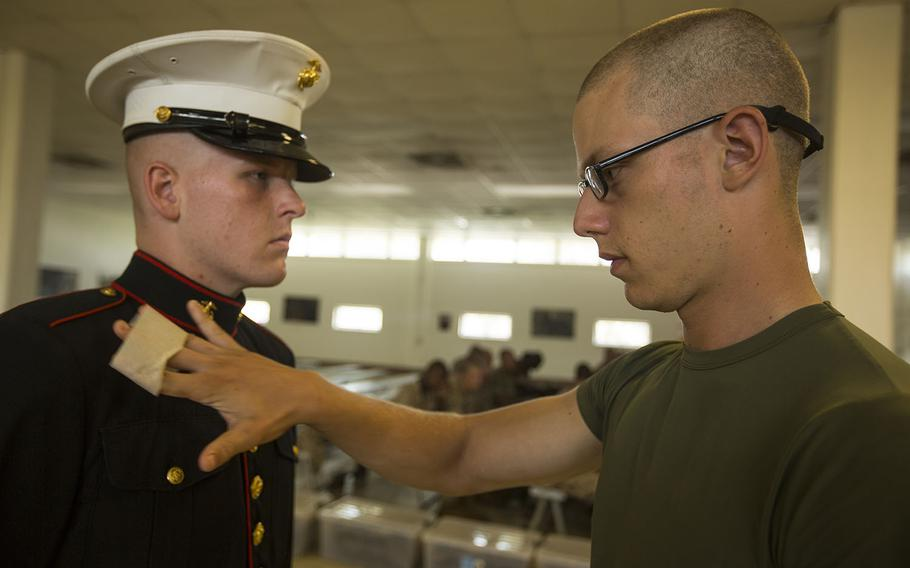 Recruit Robert J. Reynolds removes lint from a fellow recruit?s uniform before his boot camp photo is taken July 8, 2015, on Parris Island, S.C.