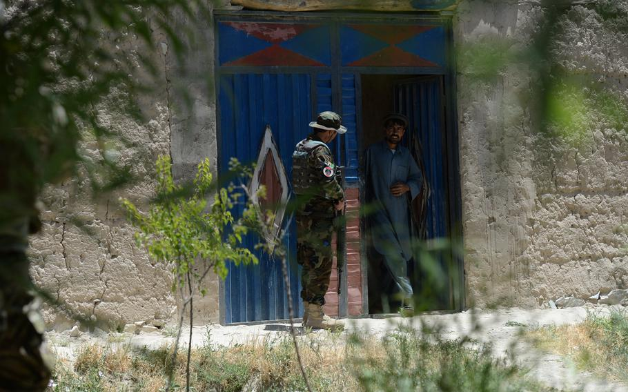 An Afghan Army officer questions a villager about a suspected rocket position in the area during a June 10, 2015, security patrol in Parwan province, central Afghanistan.