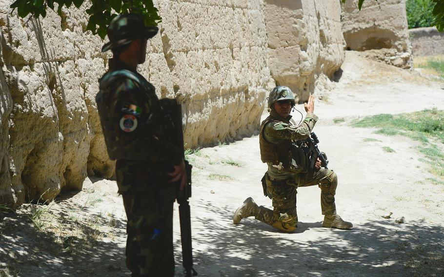 Master Sgt. Gogita Getia, 43rd Georgian Light Infantry Battalion, directs Afghan troops into position around a compound outside Bagram Air Field during a June 10, 2015, force protection mission in Parwan province, central Afghanistan.