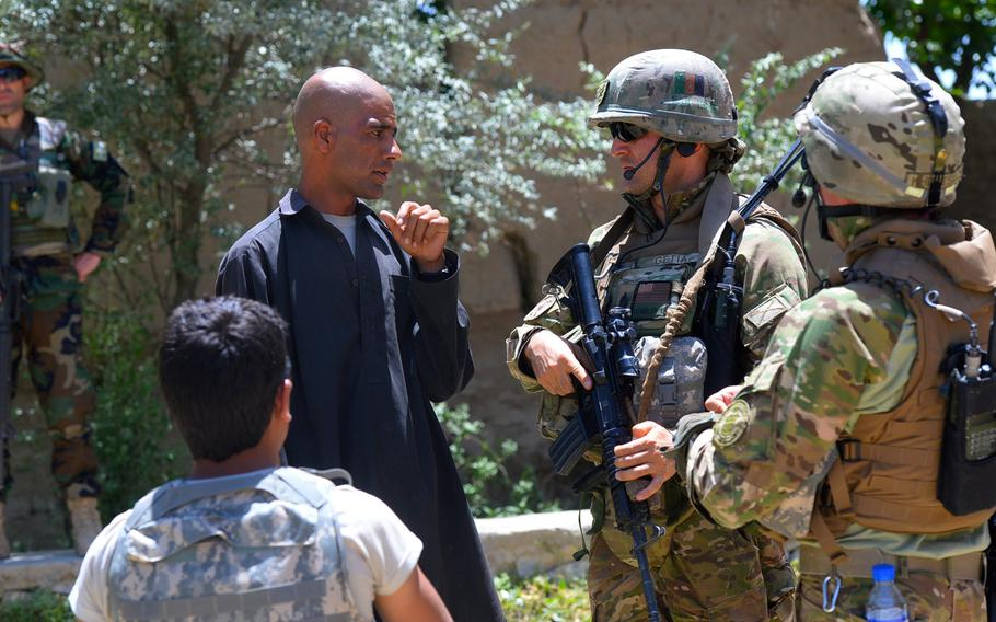 """Master Sgt. Gogita Getia, 43rd Georgian Light Infantry Battalion, questions an Afghan local on the whereabouts of several """"persons of interest"""" during a June 10, 2015, joint security patrol with U.S. forces in Parwan province, central Afghanistan."""