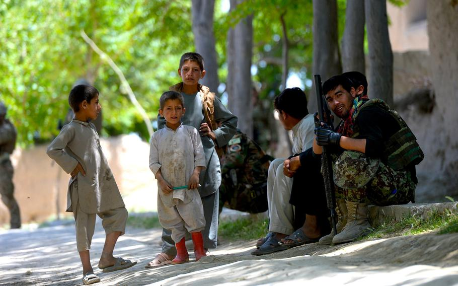 An Afghan soldier takes a break to joke with local children during a June 10, 2015, force protection patrol with U.S. and NATO forces in Parwan province, central Afghanistan.