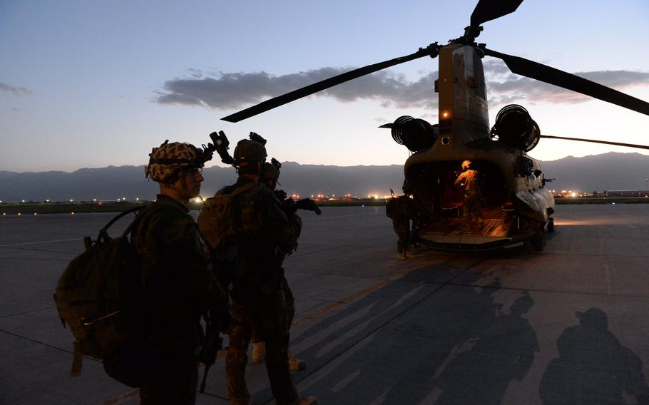 American and Czech troops wait to board an U.S. Army Chinook at Bagram Air Field during a June 3, 2015, nighttime reconnaissance patrol in Parwan province, central Afghanistan.