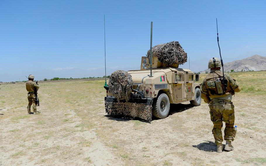 Georgian troops from the 43rd Light Infantry Battalion flank an Afghan Army Humvee during a June 10, 2015, security patrol outside Bagram Air Field in Parwan province.