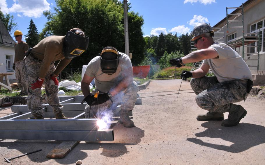 A Latvian soldier teaches Staff Sgt. John Burgh and Staff Sgt. Jason Loscar how to weld at the Naujene Orphanage, Latvia, on Monday, June 29, 2015. Burgh and Loscar are members of the 171st Air Refueling Wing Engineer Squadron team working on a humanitarian civic assistance project in Latvia.