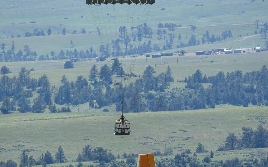 An aircrew assigned to the 153rd Airlift Wing, Wyoming Air National Guard drops a Container Delivery System bundle from a C-130H Hercules aircraft from about 5,000 feet above ground during Joint Precision Airdrop Delivery System training on Saturday, June 27, 2015, at the North Training Area, Camp Guernsey Joint Training Center, Wyo.