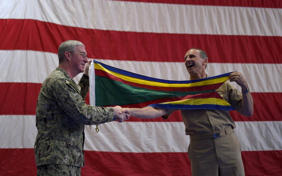 Vice Adm. John Miller, commander of U.S. Naval Forces Central Command and U.S. 5th Fleet, left, shares a laugh and shakes hands with Chief of Naval Operations Adm. Jonathan Greenert, right, after receiving the Navy Unit Commendation on behalf of his command during an all-hands call in Bahrain Monday, July 13, 2015.