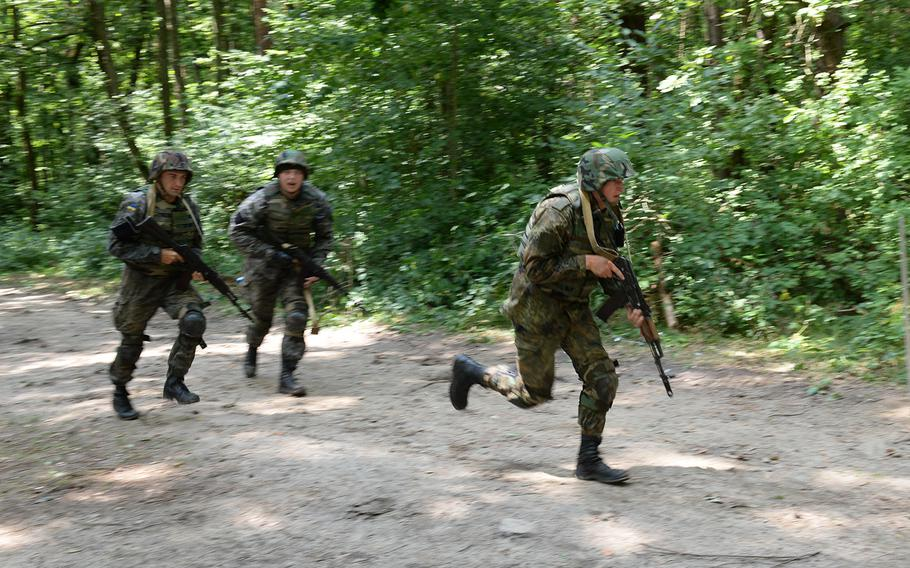 Ukrainian national guardsmen run across a simulated danger area July 9, 2015, at a training facility in Yavoriv, Ukraine. Since April, about 300 American paratroops have been training Ukrainian soldiers to fight against Russian-backed separatists in eastern Ukraine.