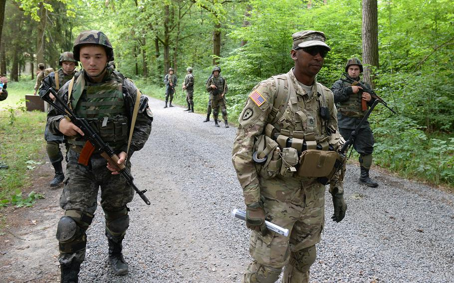 U.S. Army Staff Sgt. Gregory Simmons, center, supervises Ukrainian national guardsmen on  a simulated patrol July 9, 2105 at a training facility in Yavoriv, Ukraine. The Pentagon is considering a plan to expand the training mission to include Ukrainian army soldiers.