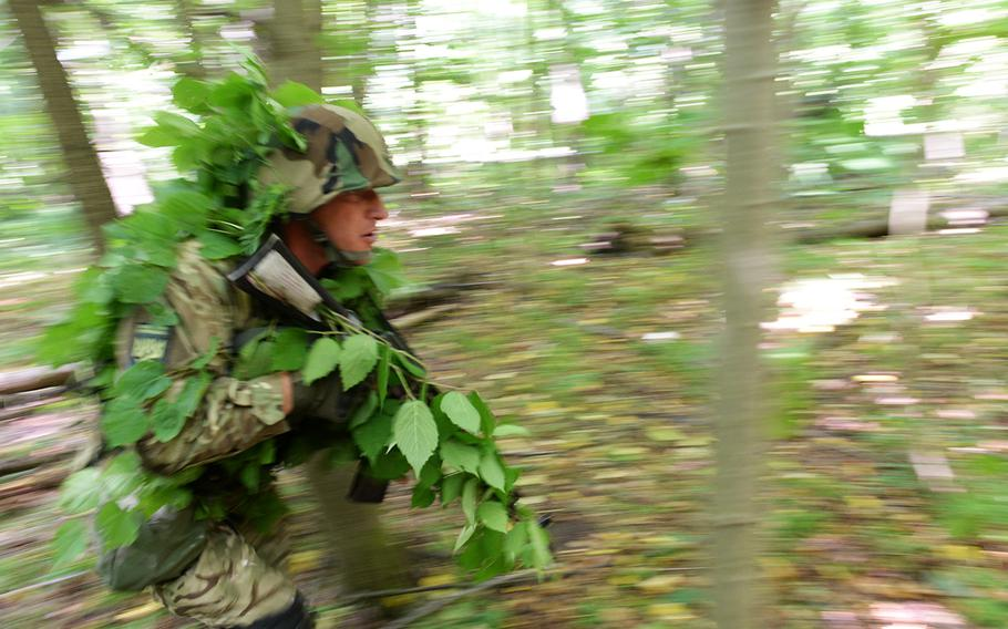 A Ukrainian national guardsman, wearing camouflage, reacts to a simulated attack July 9, 2015, at a training facility in Yavoriv, Ukraine. Because of its fight against Russian-backed separatists, Ukrainian forces have more recently used conventional warfare tactics than the U.S. soldiers sent here to train with them.