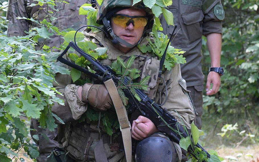 Cpl. Colt Smith, left, a paratrooper with the 173 Airborne Brigade Combat Team, and a Ukrainian translator stand behind a Ukrainian national guardsman undergoing training during a patrol July 9, 2015, at a training facility in western Ukraine.