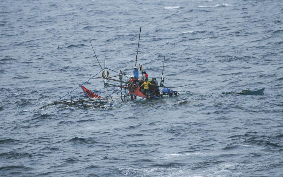 Stranded Filipino fishermen await rescue from their sinking fishing vessel by the USNS Impeccable in the South China Sea on July 19, 2015.