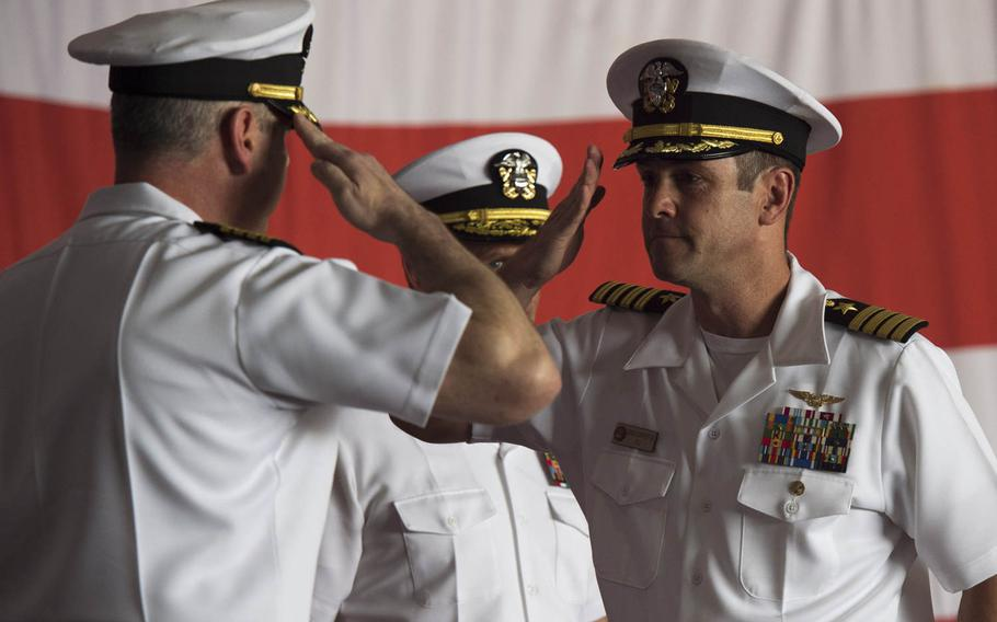 Capt. Daniel C. Grieco, outgoing commanding officer, left, salutes Capt. Craig A. Clapperton, incoming commanding officer, right, for the aircraft carrier USS Theodore Roosevelt during a change of command ceremony  in Bahrain Tuesday, July 21, 2015.