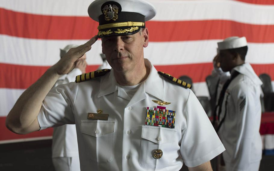 Capt. Daniel C. Grieco, USS Theodore Roosevelt's outgoing commander, salutes as he's ceremoniously rung off the aicraft carrier one last time Tuesday, July 21, 2015.  Commanding Officers are rung on and off their ship as they arrive and depart.  The Roosevelt and its carrier strike group both got new commanders Tuesday during a ceremony in Bahrain.