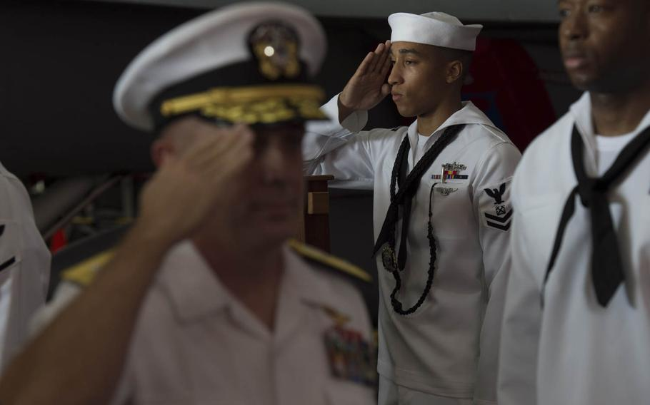 A sideboy salutes as the incoming Roosevelt carrier strike group commander, Rear Adm. Roy J. Kelley, is ceremoniously rung onto the aircraft carrier USS Theodore Roosevelt Tuesday, July 21, 2015.  Officers of a higher paygrade than the ship's commanding officer are rung on and off the ship when arriving and departing.  The Roosevelt and its carrier strike group both got new commanders during a change of command ceremony held in Bahrain.