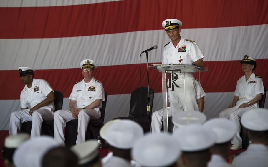 Rear Adm. Andrew L. Lewis, outgoing commander of the Roosevelt carrier strike group, makes remarks during a change of command ceremony aboard the aircraft carrier USS Theodore Roosevelt Tuesday, July 21, 2015.  The Roosevelt and its carrier strike group both got new commanders while the ship is in Bahrain on a short break from an eight-month deployment in the Middle East.