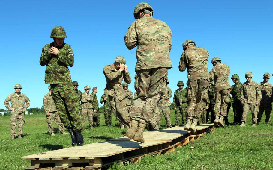 Soldiers with 2nd Battalion, 503rd Infantry Regiment, 173rd Airborne Brigade, join their Estonian counterparts while practicing landing procedures in preparation for a joint airborne jump at Tapa Army Base, Estonia, July 21, 2015, as part of Operation Atlantic Resolve.