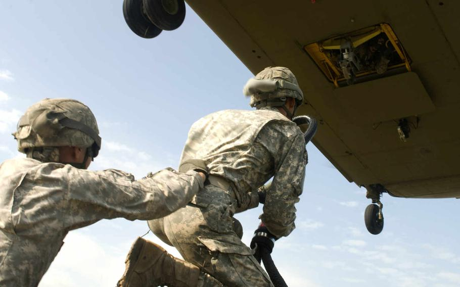 Two New York Army National Guard Soldiers from the 427th Brigade Support Battalion prepare to attach a sling load hook to a CH-47 Chinook helicopter July 19, 2015, at Fort Drum, N.Y.