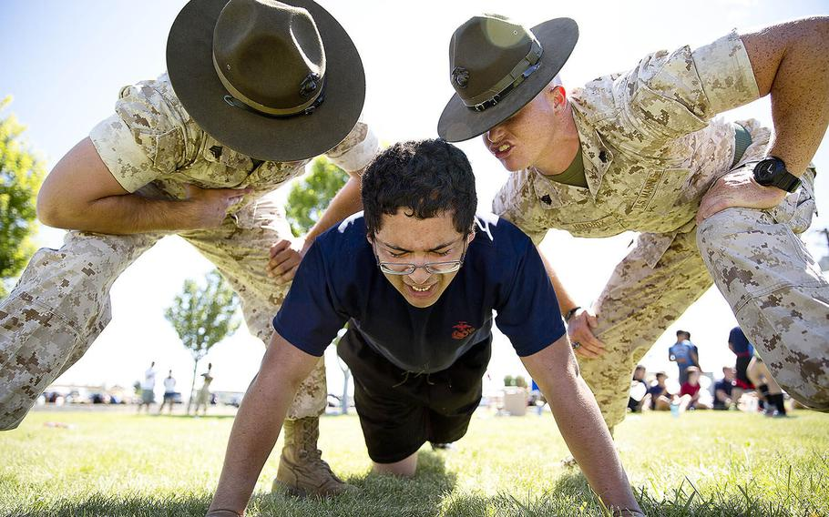Sgts. Stephen Wills, left, and Brandon Hendrix, drill instructors from Marine Corps Recruit Depot San Diego, motivate Jose Garcia, a Marine enlistee from Yakima, Wash., during a Recruiting Station Seattle pool function at the Yakima Training Center in Yakima, July 17, 2015.
