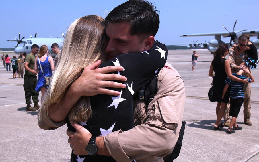 Cpl. Christopher Fuller, a crew chief with Marine Aerial Refueler Transport Squadron 252, embraces his wife, Jessica Fuller, during a return celebration for the Marines of VMGR-252 at Marine Corps Air Station Cherry Point, N.C., July 20, 2015.
