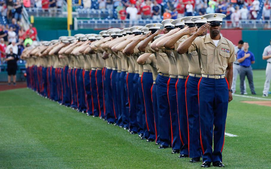 Marines from the National Capitol Region salute during the playing of the National Anthem, July 21, 2015, at Nationals Park in Washington. The Washington Nationals hosted a Marine Corps Day to honor Marines who serve and who have served in the past.
