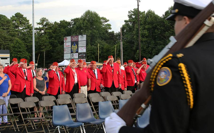 Veterans with the Marine Corps League of Woodstock, Ga., stand and salute the colors as they pass by during Lance Cpl. Squire Wells' memorial at Sprayberry High School in Marietta, Ga., July 21, 2015. Wells is one of five servicemembers to be killed when a gunman entered the Naval Operational Support Center and Marine Corps Reserve Center in Chattanooga, Tenn. on July 16, 2015.