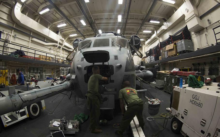 CH-53E avionics technicians with the Marine Medium Tiltrotor Squadron 162, 26th Marine Expeditionary Unit, conduct preventive maintenance on a CH-53E Super Stallion aboard the USS Arlington in the Atlantic Ocean, July 21, 2015.