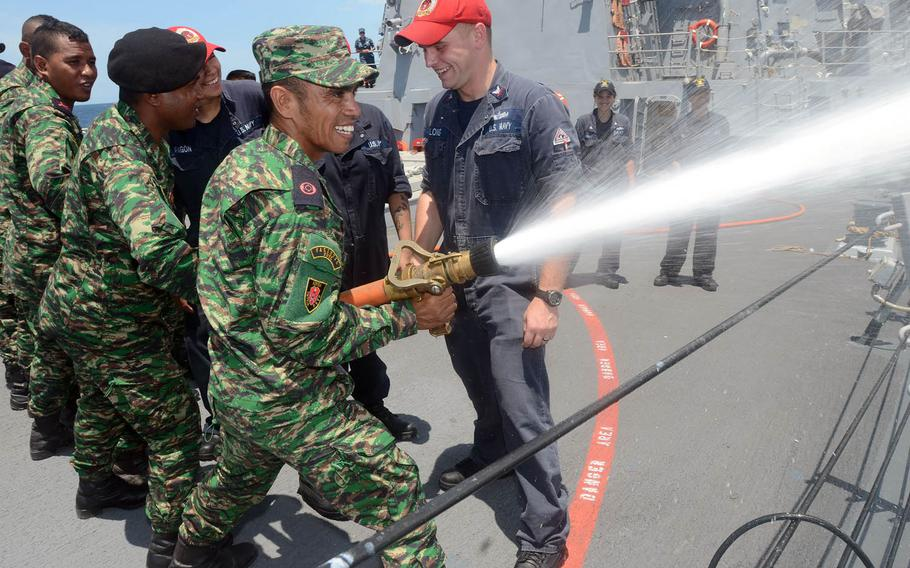 U.S. sailors help members of East Timor's Defense Force work on fire hose-handling skills aboard the guided-missile destroyer USS Kidd during 2014 Cooperation Afloat Readiness and Training (CARAT) in East Timor. About 150 U.S. sailors have arrived in East Timor for this year's CARAT exercise. Sailor will train East Timor servicemembers on basic seamanship, while Seabees will work on community service projects.