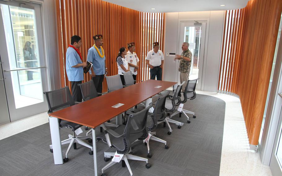 A Defense POW/MIA Accounting Agency representative tells visitors about the family viewing room at the agency's new lab, which serves as a centerpiece of the three-story building.
