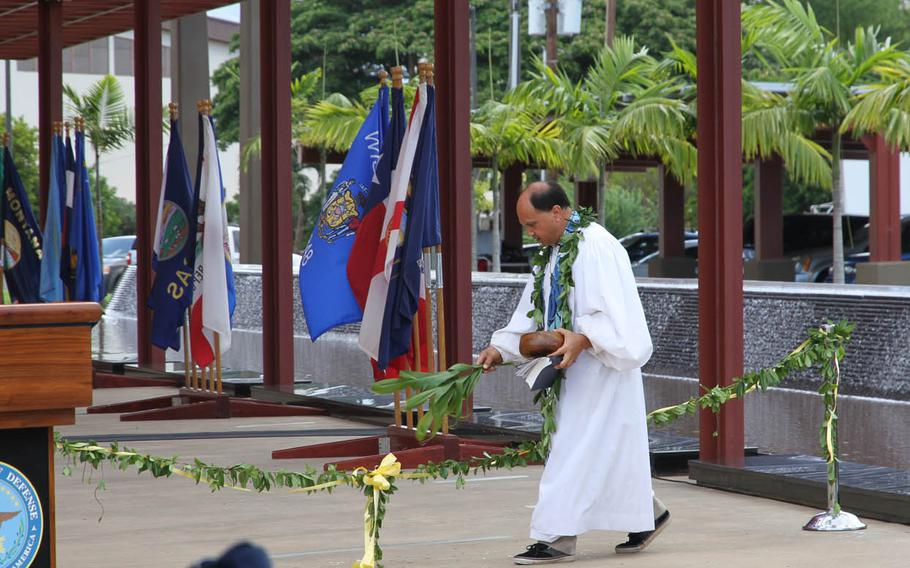 The Rev. Kahu Kordell Kekoa blesses the maile lei before guests untied it Monday, July 27, 2015, during the dedication ceremony of the Sen. Daniel K. Inouye DPAA Center of Excellence at Joint Base Pearl Harbor-Hickam in Hawaii.