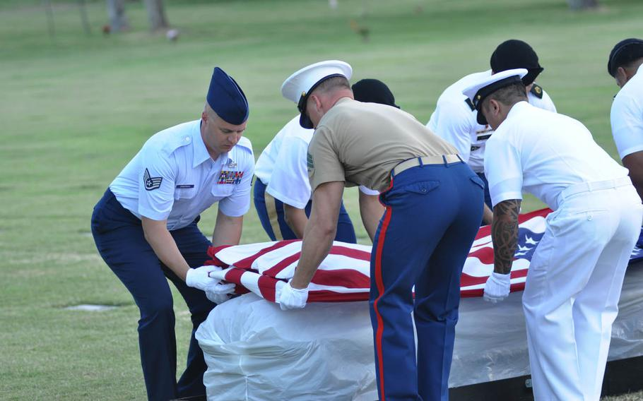 Servicemembers drape a flag over one of five caskets taken from the National Memorial Cemetery of the Pacific Monday, July 27, 2015, during a dignified transfer ceremony. The caskets contain the remains of unknown sailors and Marines who died on the USS Oklahoma on Dec. 7, 1941, and were being transferred to the Defense POW/MIA Accounting Agency for identificaiton.