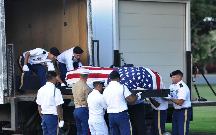 A casket holding the remains of sailors and Marines killed on the USS Oklahoma is lifted onto a truck Monday, July 27, 2015, in Honolulu during a dignified transfer ceremony.