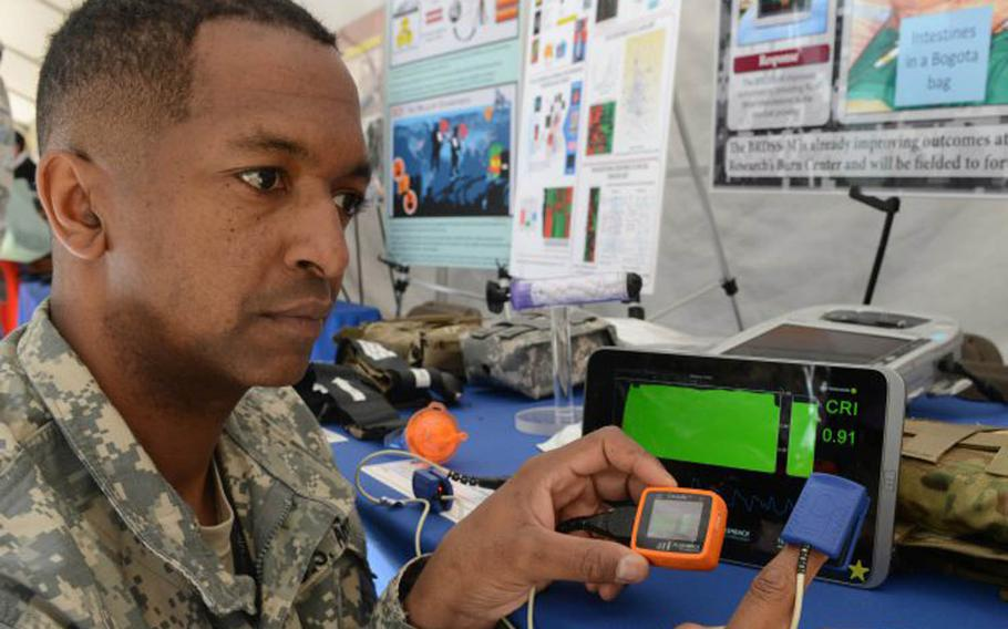 Lt. Col. Robert Carter, with the Tactical Combat Casualty Care Research program, shows the Compensatory Reserve Index, or CRI, device that could lower casualties on the battlefield by warning when shock is imminent due to blood loss. Behind the CRI is a green-screen smart tablet that can display results from multiple CRIs.