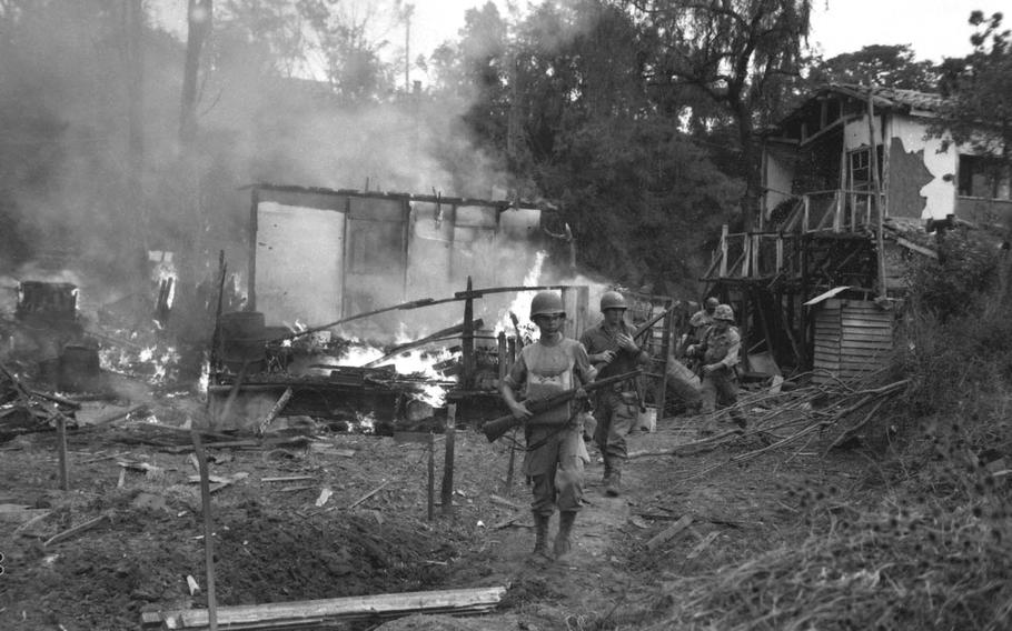 """Leathernecks lead a patrol between destroyed buildings during a """"mop up"""" of Wolmi Island, Sept. 15, 1950. Some 400 North Korean troops invaded Wolmi, and the U.S believed an attack on the island was necessary in advance of a planned amphibious assault on Incheon."""