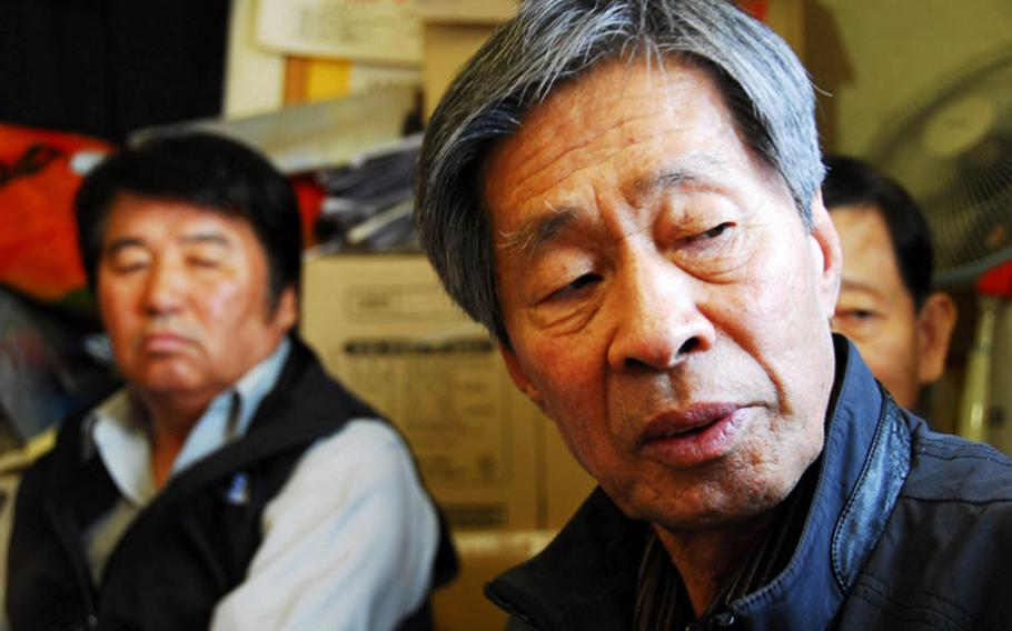 Jon Chon-bong, 78, sits inside a small building near Wolmi Park in 2011 and talks about the U.S. bombing of his village on Wolmi Island in 1950. He is one of 44 South Koreans who filed a lawsuit seeking compensation for the property their families lost in the bombing. Behind him, left, is Jeong Ji-eun, whose father died in the attack.