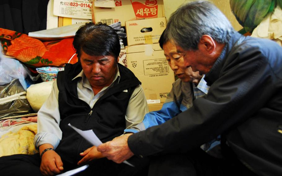 Jeong Ji-eun, from left to right, Jang Seok Ju and Jon Chon-bong look at old aerial photographs in 2011 of Wolmi Island, where they lived before the U.S. bombed the island in September 1950 to rid it of North Korean troops. The men were part of a group of approximately 160 former residents of Wolmi Island that filed suit against the government, seeking compensation for property lost during the bombing.