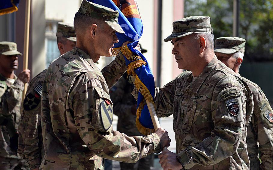 """At a ceremony in Kabul, Afghanistan, Gen. John F. Campbell, commander, Resolute Support, right, passes the unit colors to Maj. Gen. Gordon """"Skip"""" Davis, incoming commander for Combined Security Transition Command - Afghanistan. Maj. Gen. Todd T. Semonite relinquished command during the change of command ceremony Thursday, Oct. 1, 2015, in Kabul."""