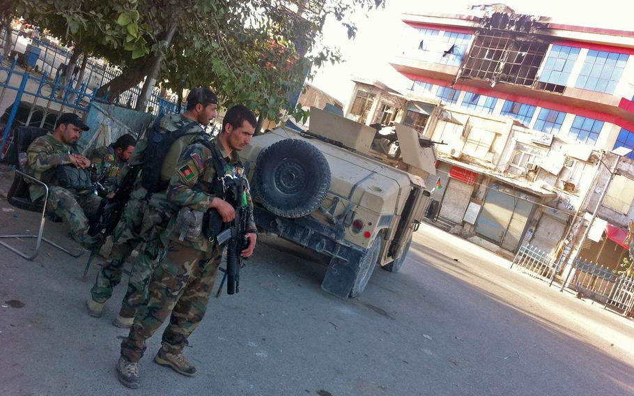 Afghan army soldiers secure a traffic circle in front of a building damaged by fighting in Kunduz city on Oct. 7, 2015. After more than a week of fighting, Afghan forces controlled some neighborhoods but continued operations to clear other areas of Taliban fighters.