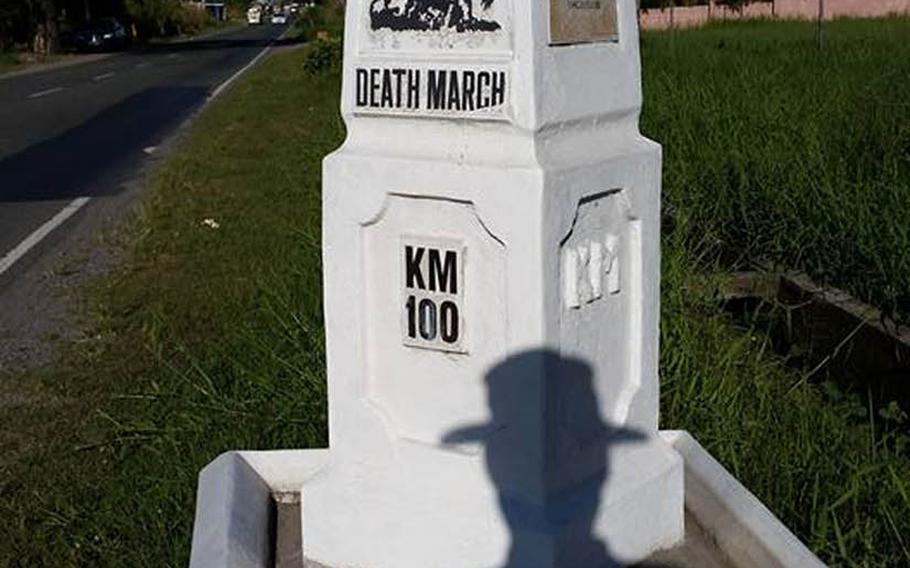 A silhouette of Tony Ahn in his boonie hat is seen as he shoots a photo of the Bataan Death March's 100-kilometer marker, Dec. 26, 2015. Ahn recently walked the route of the deadly World War II journey in which the Imperial Japanese Army transferred between 60,000 and 80,000 American and Philippine prisoners from Mariveles, Bataan, to Camp O'Donnell in Capas, Tarlac.