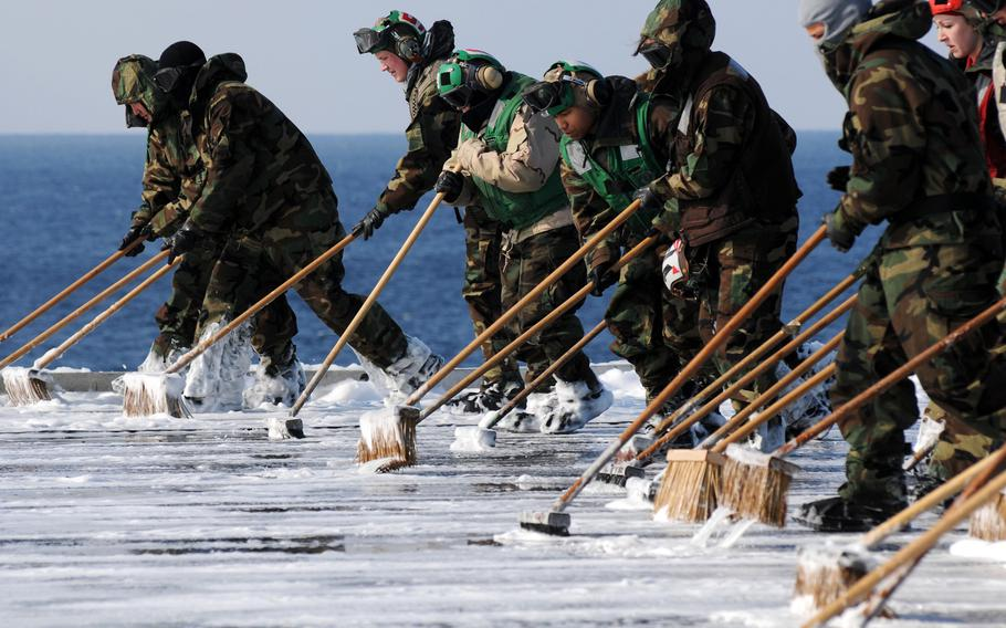 Sailors scrub the flight deck aboard the aircraft carrier USS Ronald Reagan following a countermeasure wash down to decontaminate the flight deck while the ship is operating off the coast of Japan on March 23, 2011. The Reagan, along with 15 other ships that took part in the relief effort, still have some radiation contamination more than five years later, the Navy says.