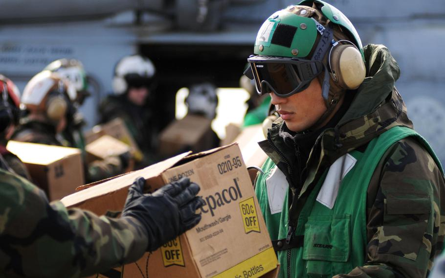 A U.S. sailor loads humanitarian assistance supplies onto an SH-60F Sea Hawk aboard the aircraft carrier USS Ronald Reagan on March 21, 2011. The Reagan, along with 15 other ships that took part in the relief effort, still have some radiation contamination more than five years later, the Navy says. Sailors aboard the ships, however, are not in any danger.