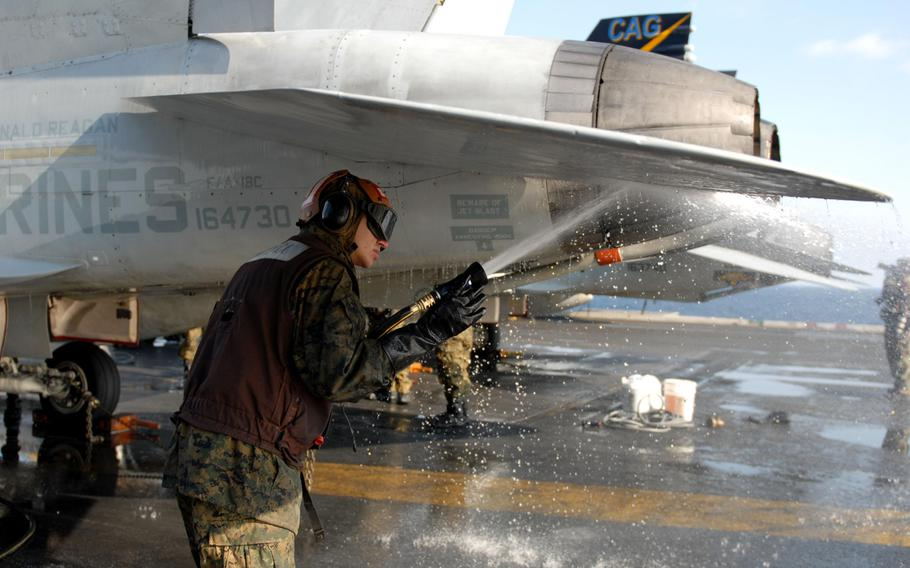 A U.S. Marine sprays the surface of an F/A-18C Hornet aboard the aircraft carrier USS Ronald Reagan during a countermeasure wash down on the flight deck in March 2011. The Reagan, along with 15 other ships that took part in the relief effort, still have some radiation contamination more than five years later, the Navy says. Sailors aboard the ships, however, are not in any danger.