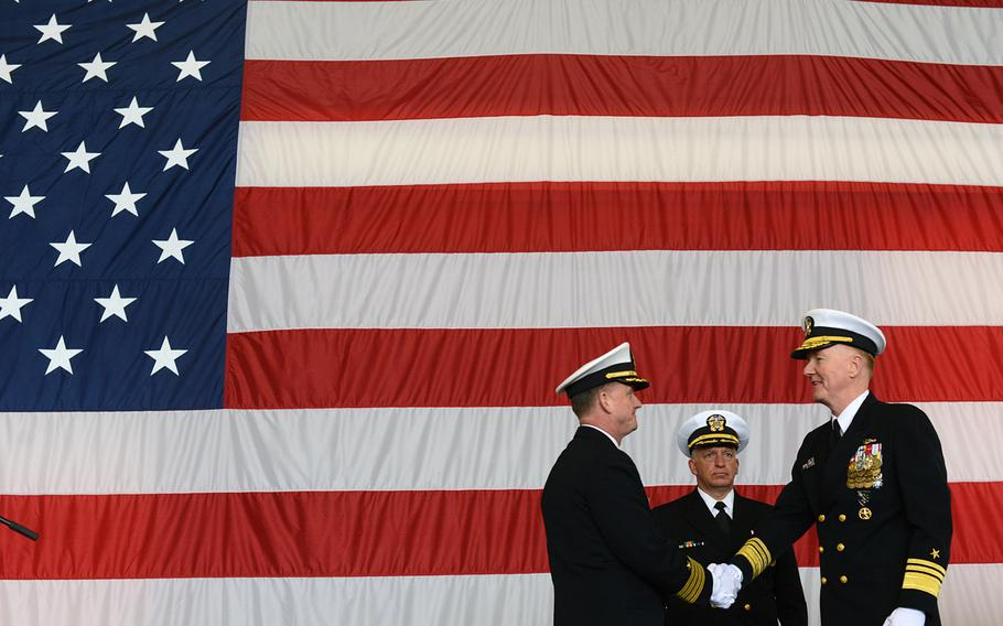 U.S. 6th Fleet Commander Vice Adm. James Foggo III, right, congratulates Capt. Jeffrey Wolstenholme, the first commander of the fleet's new Task Force 64, as Navy chaplain Capt. Wayne Macrae looks on during the task force establishment ceremony on March 24, 2016, at the Navy base in Naples, Italy.