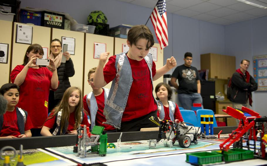 Mordecai Kenemore, a fifth-grade student at Kaiserslautern Elementary School, celebrates after his team's robot successfully completes a maneuver during a DODEA-Europe robotics competition for 10- to 14-year-old students in Kaiserslautern, Germany, on Monday, March 28, 2016.