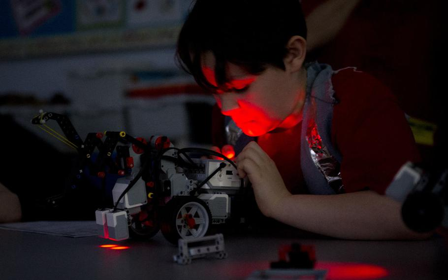 Mordecai Kenemore, a fifth-grader at Kaiserslautern Elementary School, inspects his team's robot after his turn during a DODEA-Europe robotics competition for 10- to 14-year-old students in Kaiserslautern, Germany, on Monday, March 28, 2016.