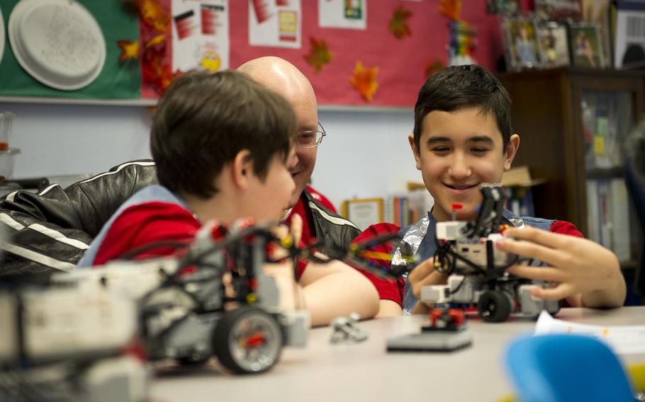 From right, Damian Harms, Matt Harms and Mordecai Kenemore, look at Damian's team's robot after a DODEA-Europe robotics competition for 10- to 14-year-old students in Kaiserslautern, Germany, on Monday, March 28, 2016. Mordecai and Damian are both fifth-graders at Kaiserslautern Elementary School. Matt Harms is Damian's father, and also volunteered to help the students learn the programming needed to operate the robots.